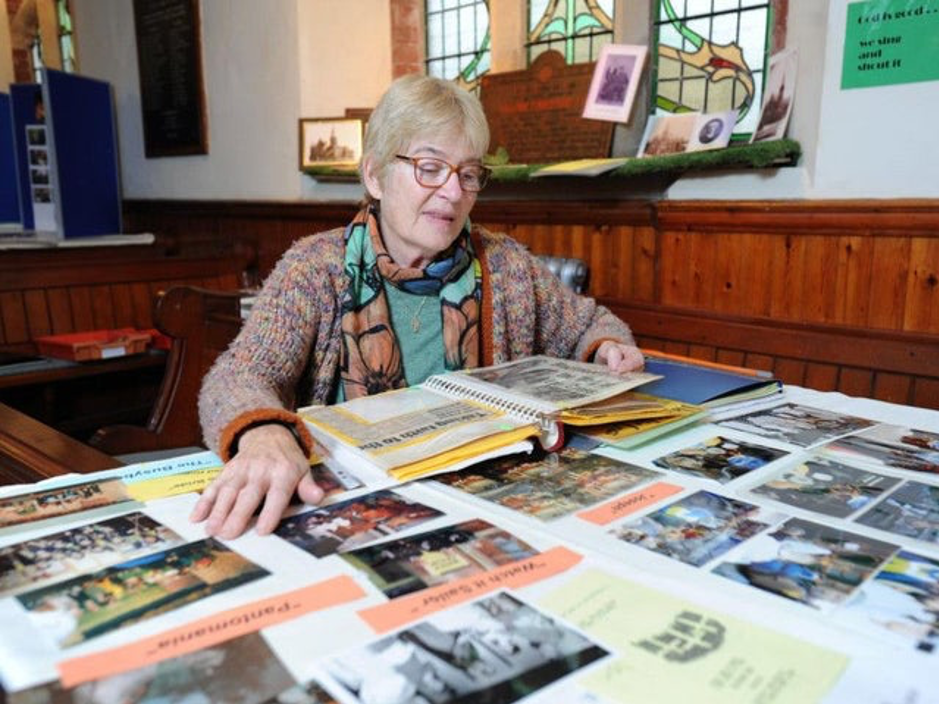 Heritage coordinator Diana Holden looking at table full of photographs